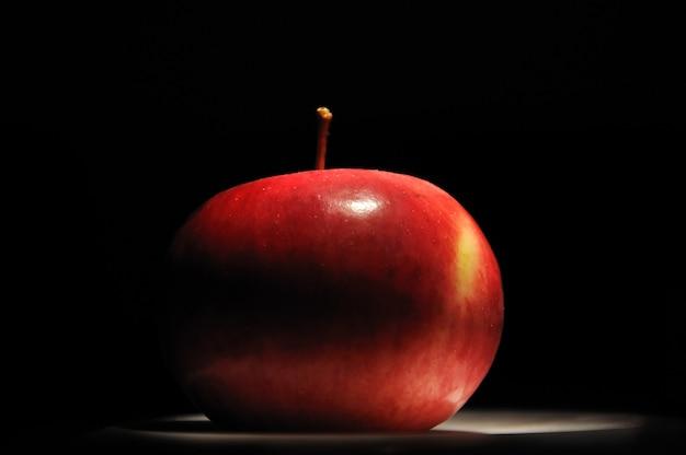 Uma maçã vermelha na escuridão