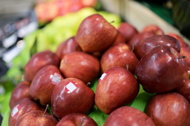 Uma maçã vermelha na prateleira de um supermercado está etiquetada.