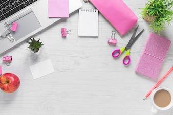 Uma maçã; xícara de chá e material de escritório com laptop no plano de fundo texturizado de madeira