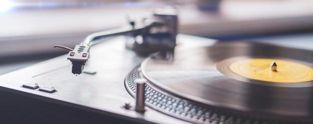 Uma macro close-up da agulha do toca-discos tocando o antigo reprodutor de música retro do disco de vinil