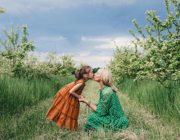 Uma mãe amorosa beija sua filha nos lábios estou em um jardim de primavera de macieira. relacionamentos familiares felizes