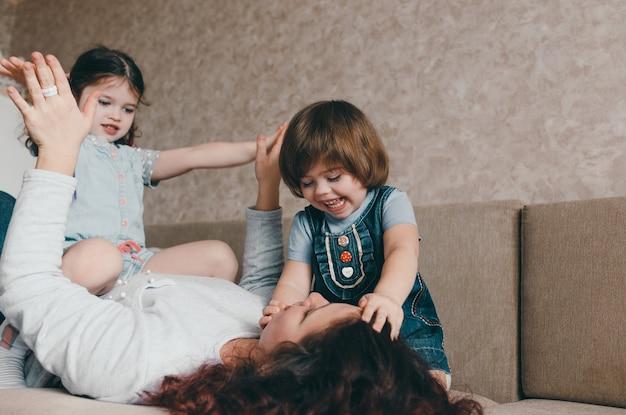 Uma mãe amorosa brinca com suas filhas deitadas no sofá. família feliz