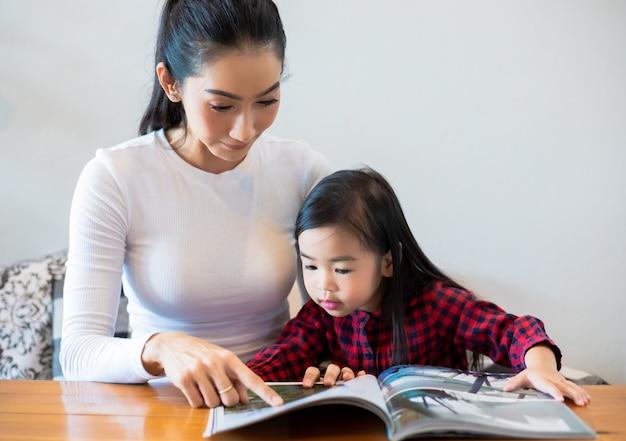 Uma mãe asiática está ensinando a filha a ler um livro durante o semestre na mesa da sala e tomando leite frio na mesa em casa. conceitos e atividades educacionais da família