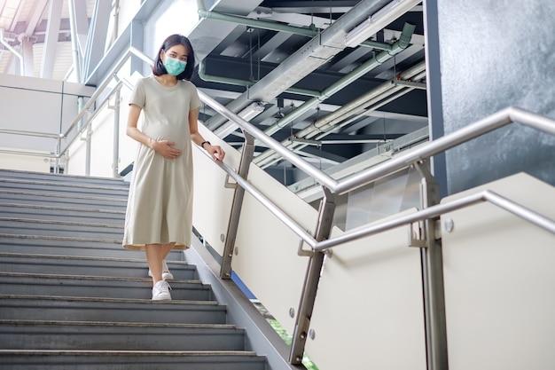 Uma mãe asiática grávida com um vestido longo descia as escadas com cautela.