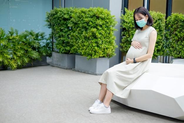 Uma mãe asiática grávida com um vestido longo está usando uma máscara e se sentando depois de ser vacinada.