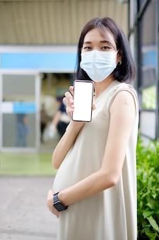 Uma mãe asiática grávida com um vestido longo mostra a tela do smartphone e o gesso após receber a vacina.