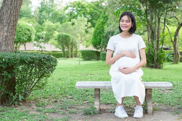 Uma mãe asiática grávida em um longo vestido branco senta-se alegremente segurando a barriga no jardim.