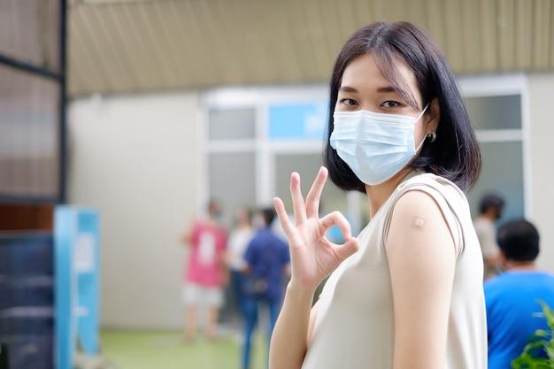 Uma mãe asiática grávida em um vestido longo está de pé para mostrar seu gesto de ok e mostrando o gesso após receber a vacinação.