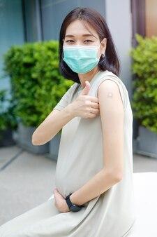 Uma mãe asiática grávida em um vestido longo está usando uma máscara e polegar para cima após ser vacinada no serviço nacional de saúde. Foto Premium