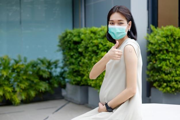 Uma mãe asiática grávida em um vestido longo está usando uma máscara e polegar para cima após ser vacinada.