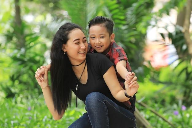 Uma mãe brinca alegremente com seu filho no parque da cidade