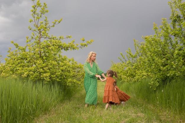 Uma mãe carinhosa brinca com suas filhas em um jardim verdejante. alegrias familiares