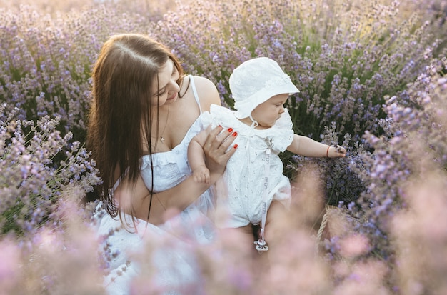 Uma mãe com a filha no campo de lavanda e eles estão felizes