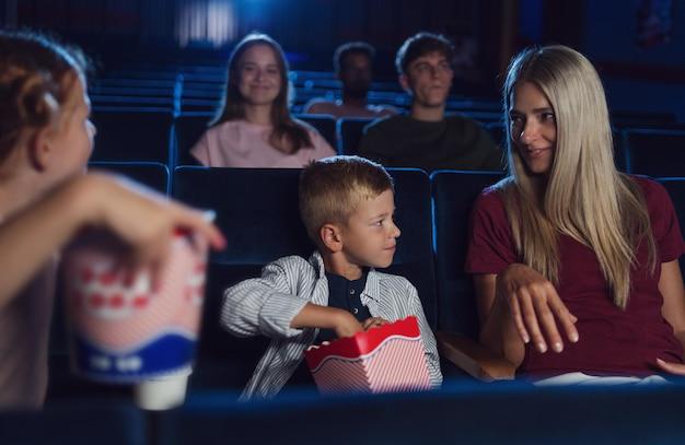 Uma mãe com filhos pequenos felizes no cinema, assistindo filme e comendo pipoca.