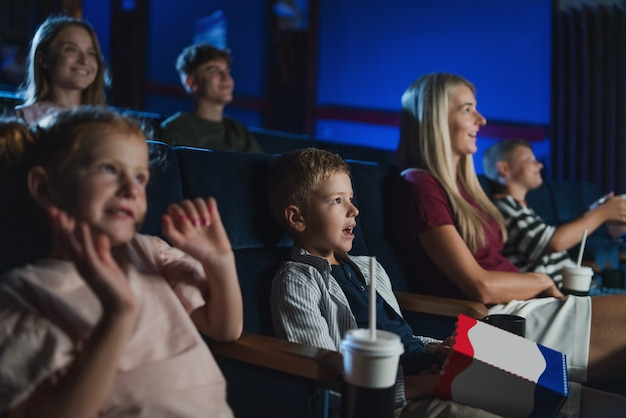 Uma mãe com filhos pequenos felizes no cinema, assistindo filme.