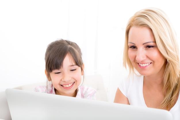 Uma mãe com sua filha olhando para um laptop em casa.