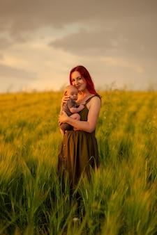Uma mãe com ternura segura o filho de três meses nos braços em um campo de trigo.