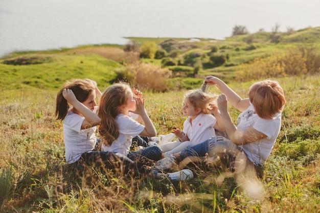 Uma mãe com três filhas senta-se na grama na praia no verão