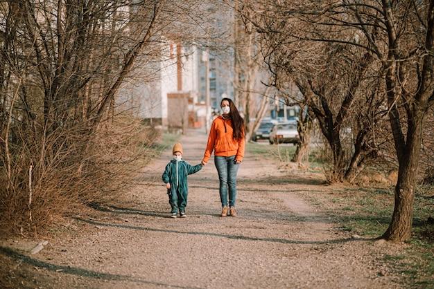 Uma mãe com um bebê em máscaras médicas caminha pela rua durante a pandemia de coronavírus e covid -19.