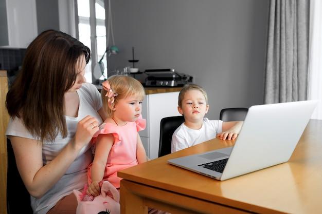 Uma mãe com um filho e filha assistindo programas educacionais em um laptop.