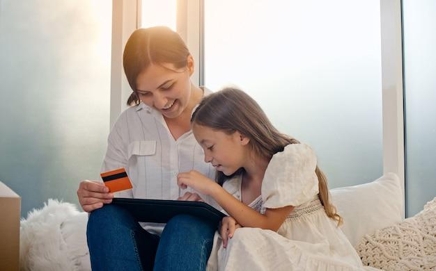 Uma mãe com um filho usa um cartão de crédito para fazer compras online e a confirmação de compra online usa um tablet t ...