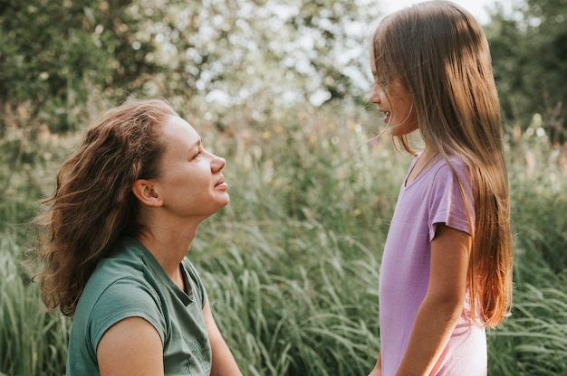 Uma mãe com um pequeno aparelho auditivo intra-canal se comunica com sua filha na natureza ao ar livre
