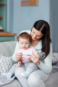 Uma mãe com uma criança doente nos braços verifica a temperatura em um termômetro