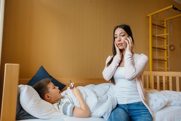 Uma mãe cuida de seu filho com febre e febre. doenças e cuidados de saúde.