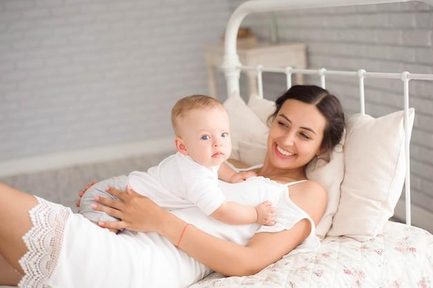 Uma mãe e bebê criança em uma cama branca.
