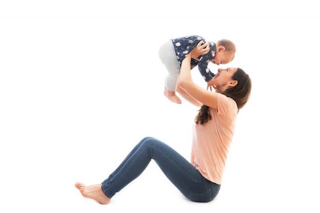 Uma mãe e bebê ginástica, exercícios de ioga, isolados no fundo branco