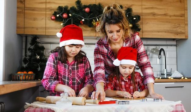 Uma mãe e duas filhas com camisas xadrez vermelhas e chapéus vermelhos aprendem a fazer biscoitos na cozinha decorada para o natal