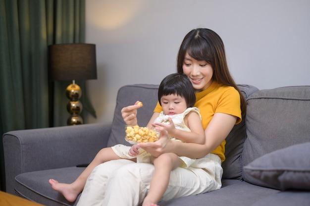 Uma mãe e filha felizes assistindo filme e relaxando em casa
