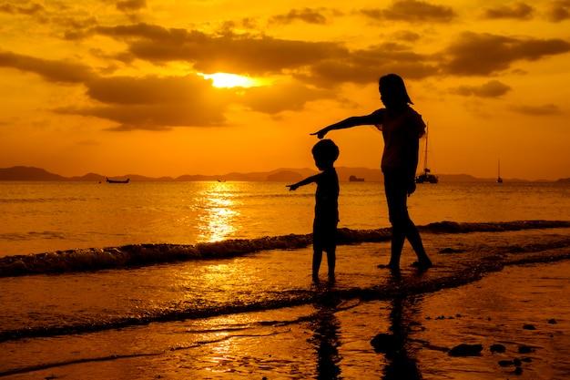 Uma mãe e filho ao ar livre ao pôr do sol com cópia espaço
