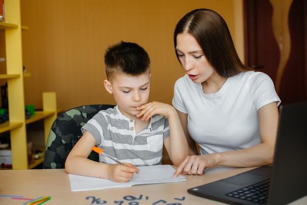 Uma mãe e seu filho estão envolvidos em ensino à distância em casa, na frente do computador. fique em casa, treinando.