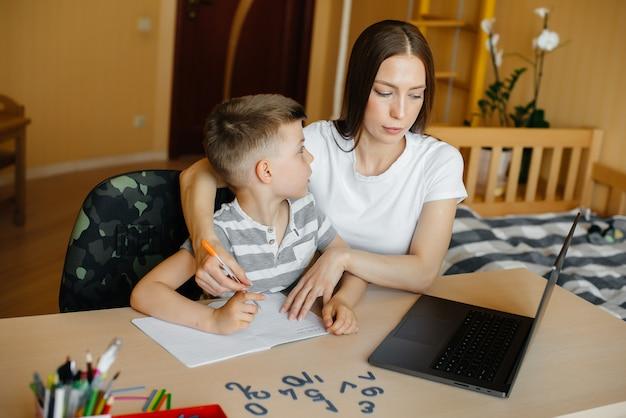 Uma mãe e seu filho estão envolvidos em ensino à distância em casa, na frente do computador.