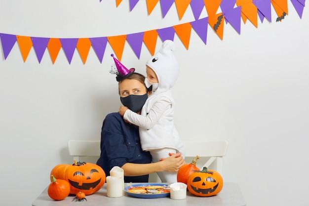 Uma mãe e sua filha no halloween a família usa máscaras que protegem contra covid19