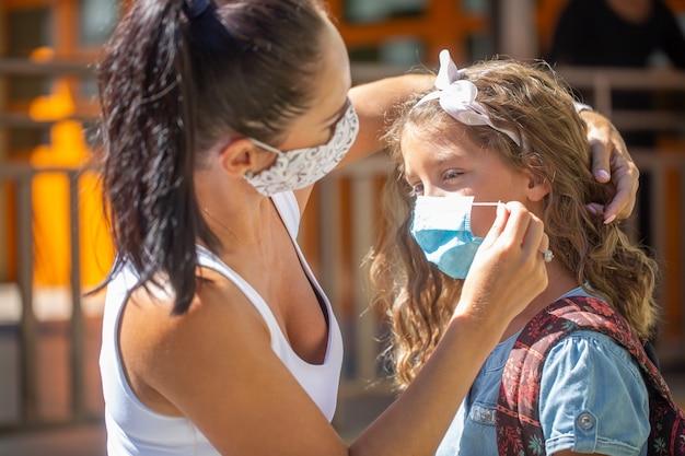Uma mãe e sua filha usam uma máscara protetora ao retornar à escola durante a quarentena de covid-19.