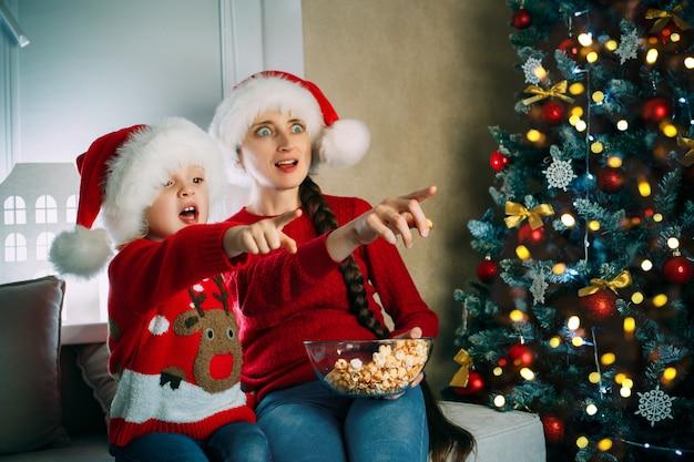 Uma mãe e sua filha usando chapéus de papai noel assistem a filmes em casa no dia de natal apontando para a tela