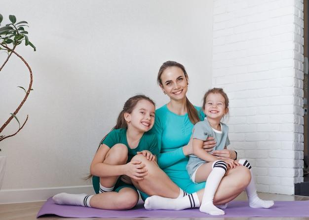 Uma mãe e suas filhas estão sentadas no chão em uniformes esportivos