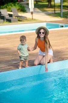 Uma mãe e um menino perto da piscina