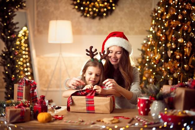 Uma mãe e uma família felizes embalam presentes de natal