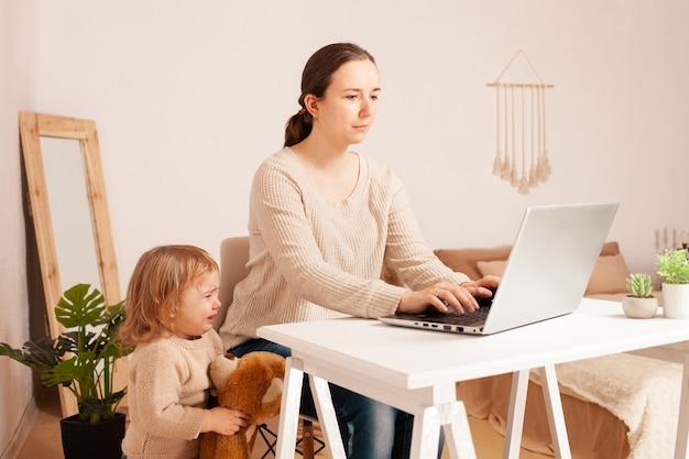 Uma mãe em licença maternidade senta-se em um laptop e trabalha uma criança gritando histericamente distrai