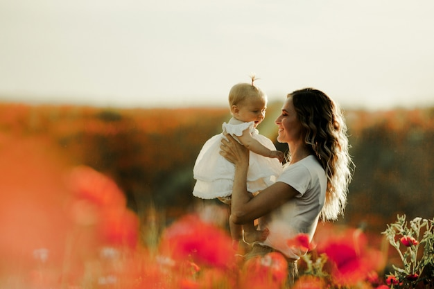 Uma mãe está segurando um bebê e sorri para ela