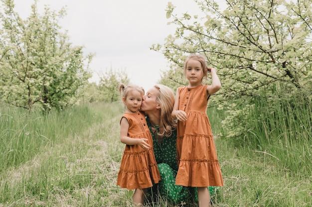 Uma mãe feliz abraça e beija as meninas em um jardim verde primavera. passeio de primavera no parque com as crianças.