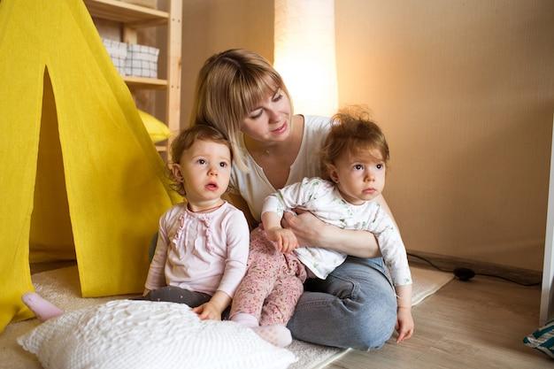 Uma mãe feliz com duas meninas gêmeas brinca em casa no chão, sentada perto de uma tenda amarela. jogos conjuntos de mães e filhas.
