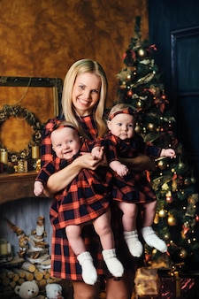 Uma mãe feliz com seus filhos gêmeos no interior da casa de ano novo no fundo de uma árvore de natal.