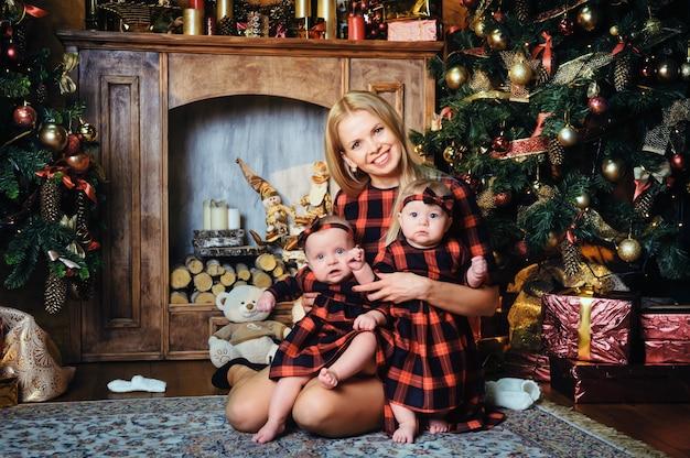 Uma mãe feliz com seus filhos gêmeos no interior de uma casa de ano novo no fundo de uma árvore de natal