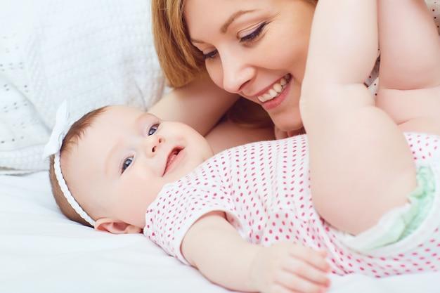 Uma mãe feliz com um bebê joga em uma cama em uma sala dentro de casa. dia das mães.