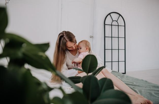 Uma mãe feliz com uma filha se abraça na cama do quarto