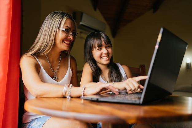 Uma mãe feliz e alegre e sua filhinha curiosa estão usando um laptop para assistir a desenhos animados, a menina está apontando para o monitor.